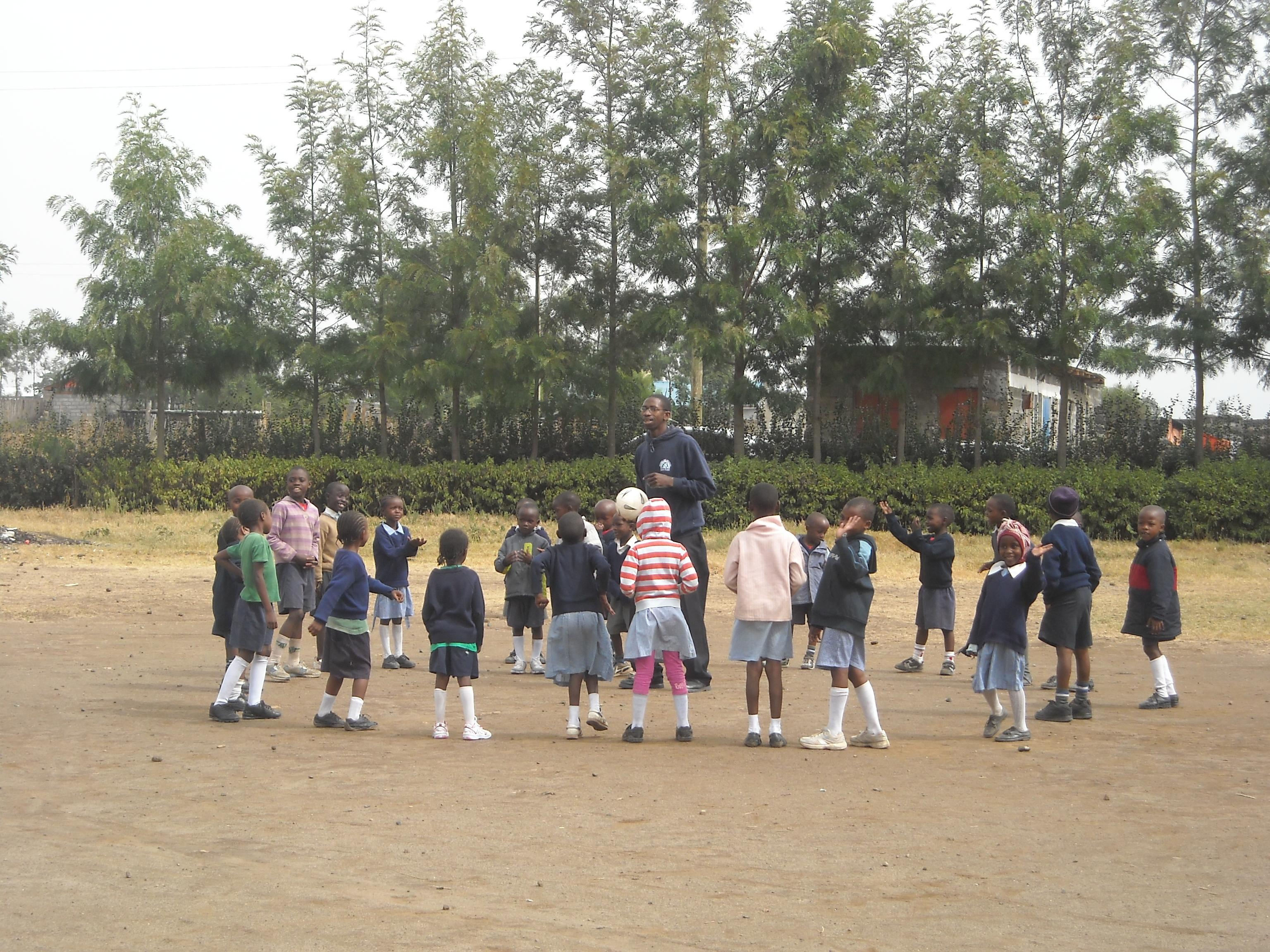 Volunteers and students stand in a circle while playing a game at the volunteer teaching placement in Kenya